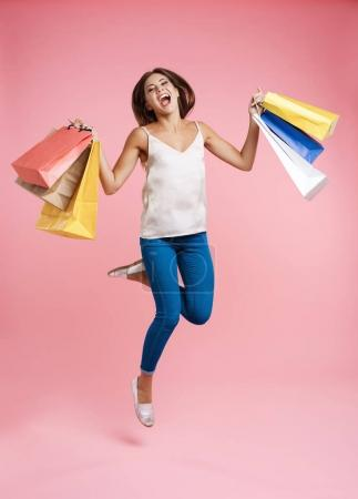 Happy shopping woman jumping up with bunch of shopping bags