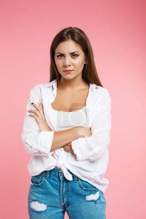 Angry woman shows irritation looking straight at camera without smile