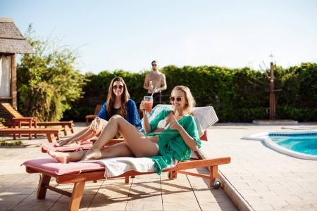 Girls smiling, drinking cocktails, sunbathing, lying near swimming pool.