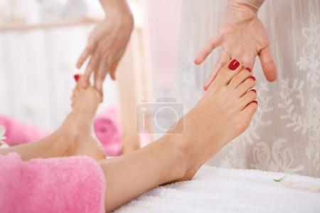 Careful female messeur giving foot massage in bright room