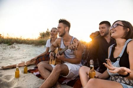 Young company of friends rejoicing, resting at beach during sunrise.