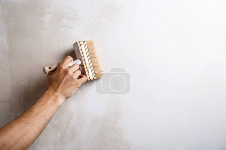 Close up of hand painting wall with brush. Copy space.