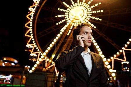 Photo pour Portrait de jeune homme d'affaires prospère en costume, s'exprimant au téléphone au parc d'attractions de nuit. - image libre de droit