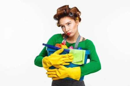 Young pretty woman holds cleaning tools with sadness on face
