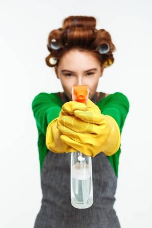 Woman points out spray at camera with yellow gloves on hands