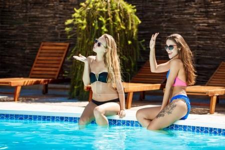 Young beautiful girls smiling, greeting, relaxing near swimming pool.