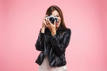 Fashion girl in black leather jacket holding old camera