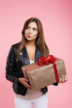 Pretty woman holding big present box looking away making faces