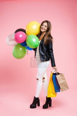 Birtday girl in amazing outfit looking straight holding gifts