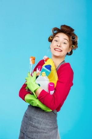 Happy housewife holds cleaning tools wearing green gloves