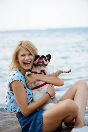 Beautiful blonde girl sitting, playing with French bulldog near sea.