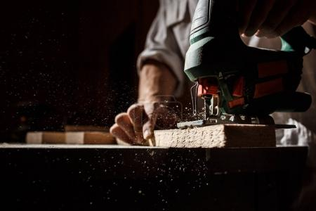 Close up photo of cutting wood with fretsaw.