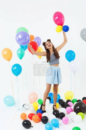 Beautiful woman on high heels looks happy playing with balloons