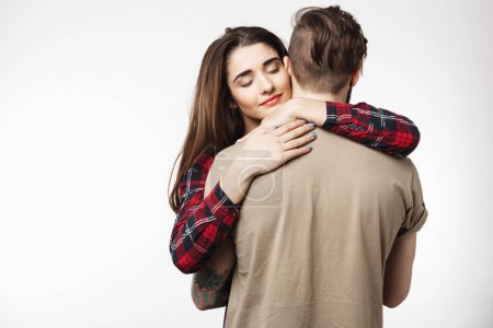 Man standing with back to camera, girlfriend hugging him romantically.