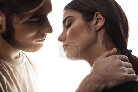 Man holding hand on womans neck. Eyes closed. Soft kiss.