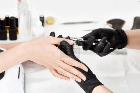 Manicurist in black gloves making manicure using manicure nipper tool.