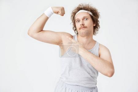 Photo pour Closeup portrait d'homme Sportswear ancienne montrant les gros canons, pointant avec la main gauche - image libre de droit