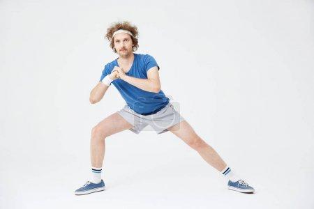 Photo pour Position de fente profonde latérale. Retro homme dans des vêtements de style vieux réchauffer les muscles de la jambe gauche - image libre de droit