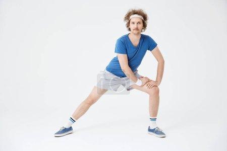 Photo pour Homme marming vers le haut. Bandeau bleu de t-shirt, blanc chaussettes, gris shorts, blanc, à la recherche de concentré - image libre de droit
