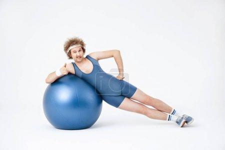Photo pour Homme travaillant sur obliques, couché sur son côté, formation avec ballon d'exercice purple big - image libre de droit