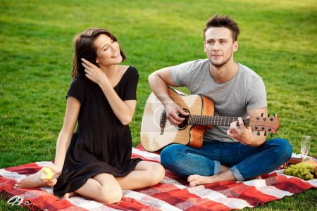 couple smiling, resting on picnic