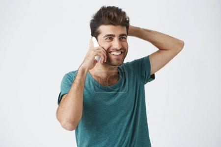 Close up isolated portrait of smiling spanish male in trendy t-shirt, smiling and holding his head, while talking on the phone with best friend.