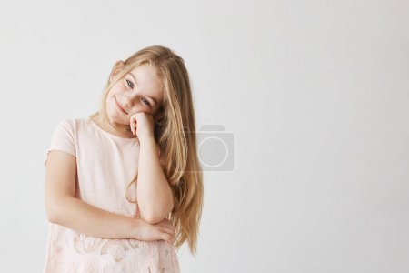 Beautiful small girl with blue eyes and light hair in cute pink dress smiles, looking at camera and holding cheek with her hand.