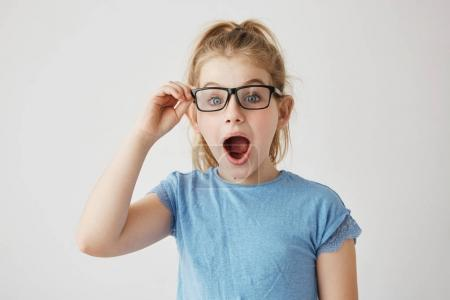 Little beautiful girl with bright blue eyes and blonde hair posing with opened mouth, holding her glasses with hand looking super surprised.