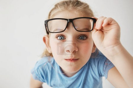 Close up portrait of curious little girl with big blue eyes standing close and looking in camera, holding glasses with hand.