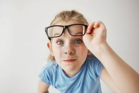 Close up portrait of cheerful small girl with blonde hair and blue eyes funny imitates adult person with glasses with surprised expression.