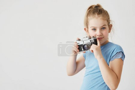 Portrait of confident young lady with blue eyes and blonde hair posing with her photo camera showing she wants to be photographer. Copy space