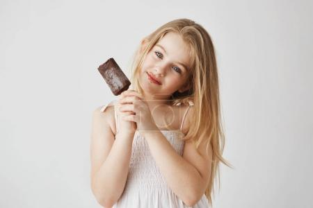 Studio portrait of joyful little girl with blue eyes and light hair enjoying her ice-cream with chocolate remains on her face. Happy and carefree childhood