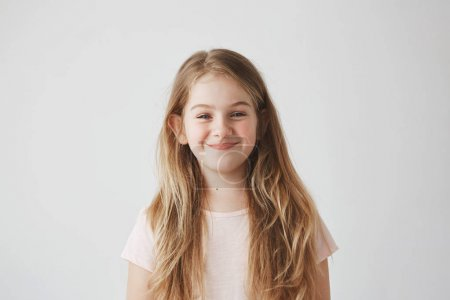 Close up of sweet little girl with light long hair and red cheeks looking in camera with foxy expression, going to make something bad.