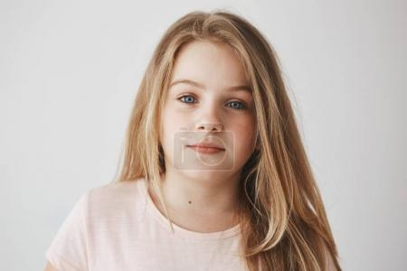 Close up of beautiful little blonde girl with light long hair and bright blue eyes. Child looking in camera with relaxed expression
