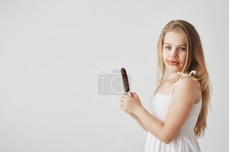 Funny cheerful little girl with light hair in white dress looking in camera with dirty face. Child already ate one ice cream and going to have one more.