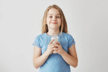 Little cute girl with blonde hair in blue t-shirt with milk drops on face, happy to start her day with big glass of healthy drink.