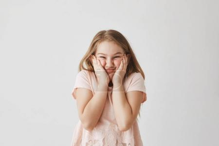 Portrait of funny blonde girl in pink dress, squeezing face with hands, making silly faces preventing mother from taking good photo of her.
