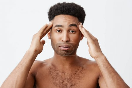 Photo for Negative emotions. Man having headache after partying all night. Close up of young dark-skinned male with afro hairstyle without clothes massaging head with hands - Royalty Free Image