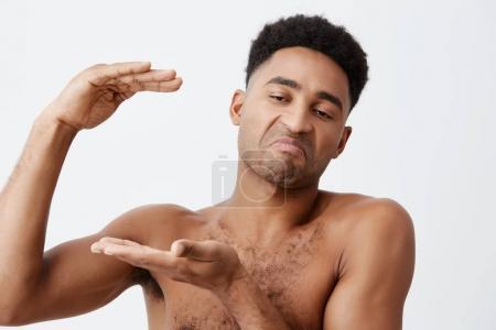 Photo pour Gros plan de jeunes hommes drôles de peau noire avec des cheveux bouclés sans vêtements gesticulant avec mains, affichage de grande taille, à la recherche de côté avec l'expression cynique - image libre de droit