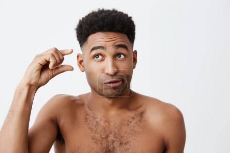 Photo pour Portrait de drôle foncée gars américain aux cheveux bouclés et sans vêtements, regardant de côté avec expression stupide et cynique, gesticulant avec la main. Émotions de peuples - image libre de droit