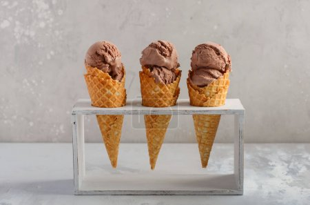 Photo for Chocolate ice cream in waffle cone on gray concrete background, selective focus. - Royalty Free Image
