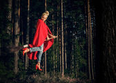 Modern angry witch in jeans and red cape flying on a broom through the forest. Levitation. Halloween holiday.