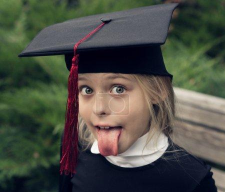 Photo pour Belle fille blonde en uniforme scolaire et casquette de fin d'études sur sa tête sort sa langue comme Albert Einstein. Éducation . - image libre de droit