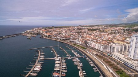 A view on Ponta Delgada from marina, Sao Miguel, Azores, Portugal. Moored yachts and boats along the port piers on a beautiful morning.