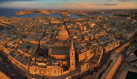 Photo pour Vue aérienne panoramique sur l'historique Trois villes au-dessus de La Valette en lumière dorée. Destination touristique. Centre historique de Malte île de l'air. Monuments en pierre de Malte éclairés par le soleil couchant - image libre de droit