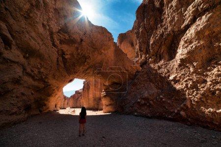 hiker walking under cliffs