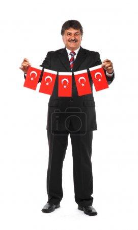mature businessman holding flags of Turkey