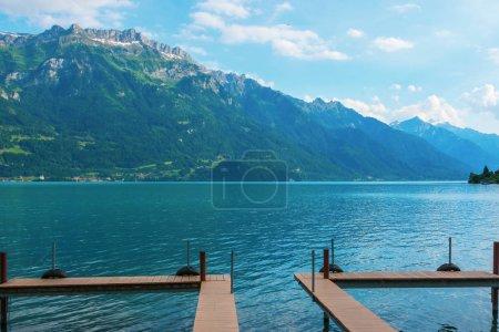 Photo pour Masse en bois sur fond d'eaux calmes turquoise et de hautes montagnes - image libre de droit