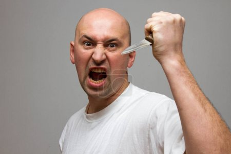 Enraged man with a knife aggressive, frustrated portrait man, holding his fist up isolated on black background.