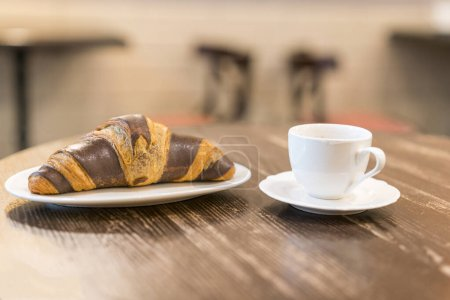 Photo for Chocolate croissant on plate in cafe and cup of espresso. - Royalty Free Image